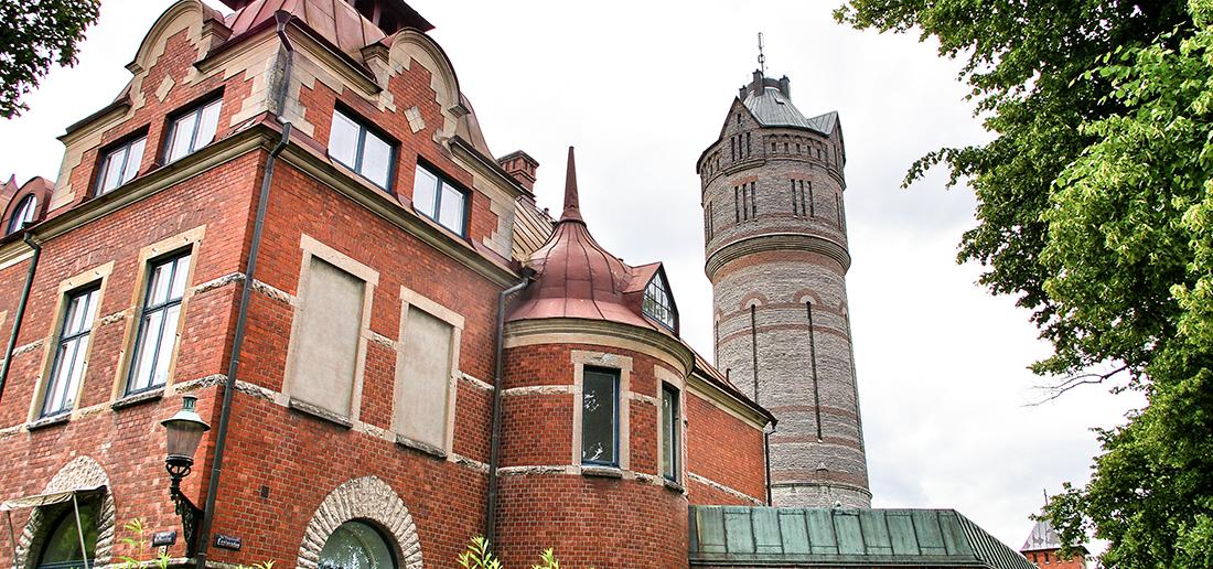 Bild på byggnad samt gamla vattentornet i Lidköping.