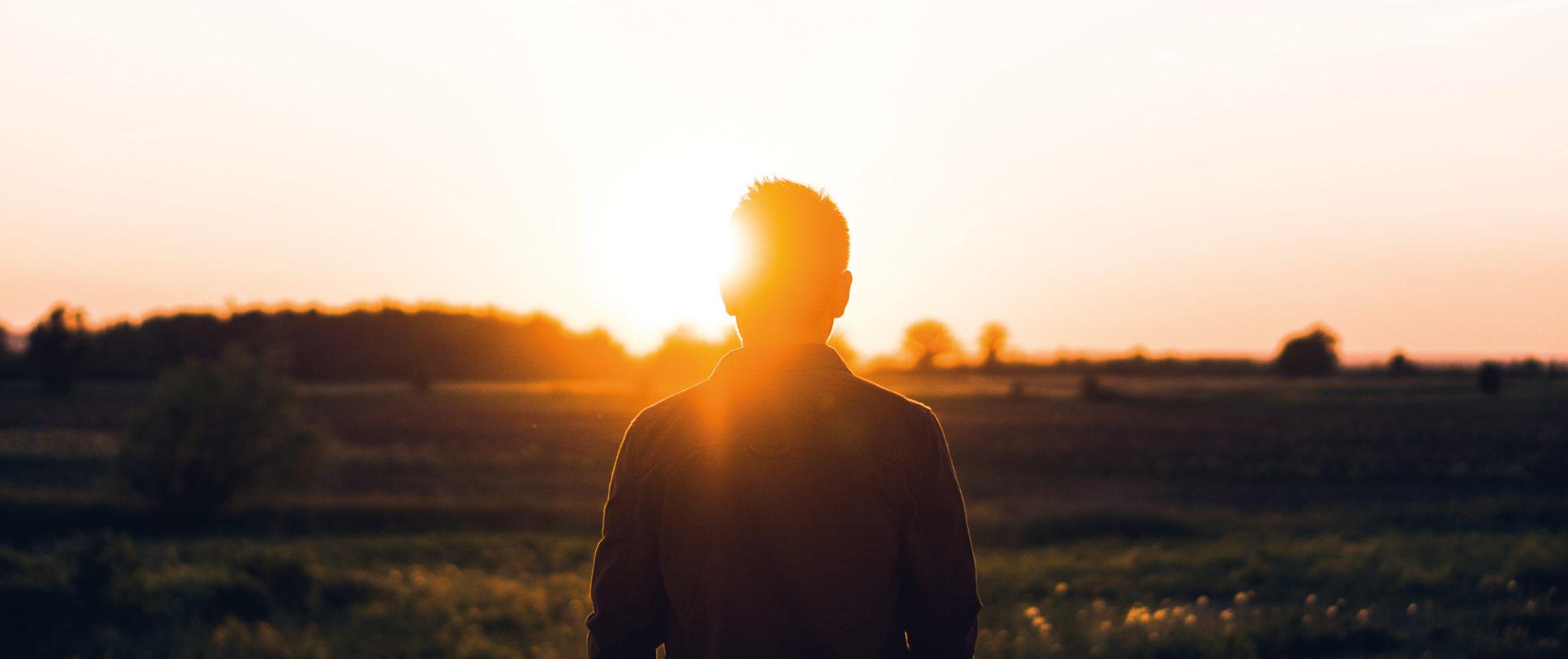 Miljöbild. Solnedgång med en man står i förgrunden.