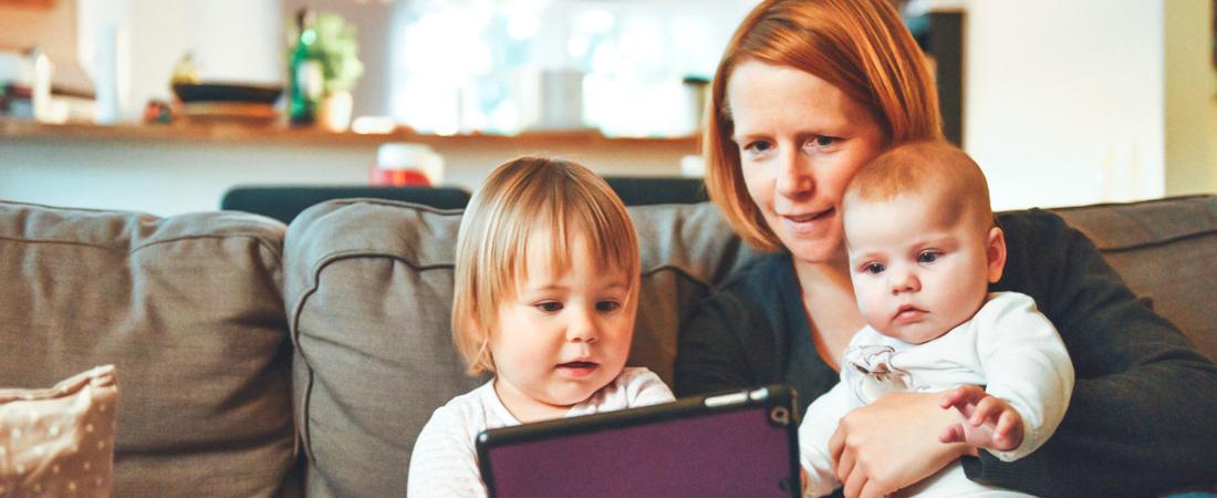 En mamma med två barn sitter i en soffa och tittar i iPad.