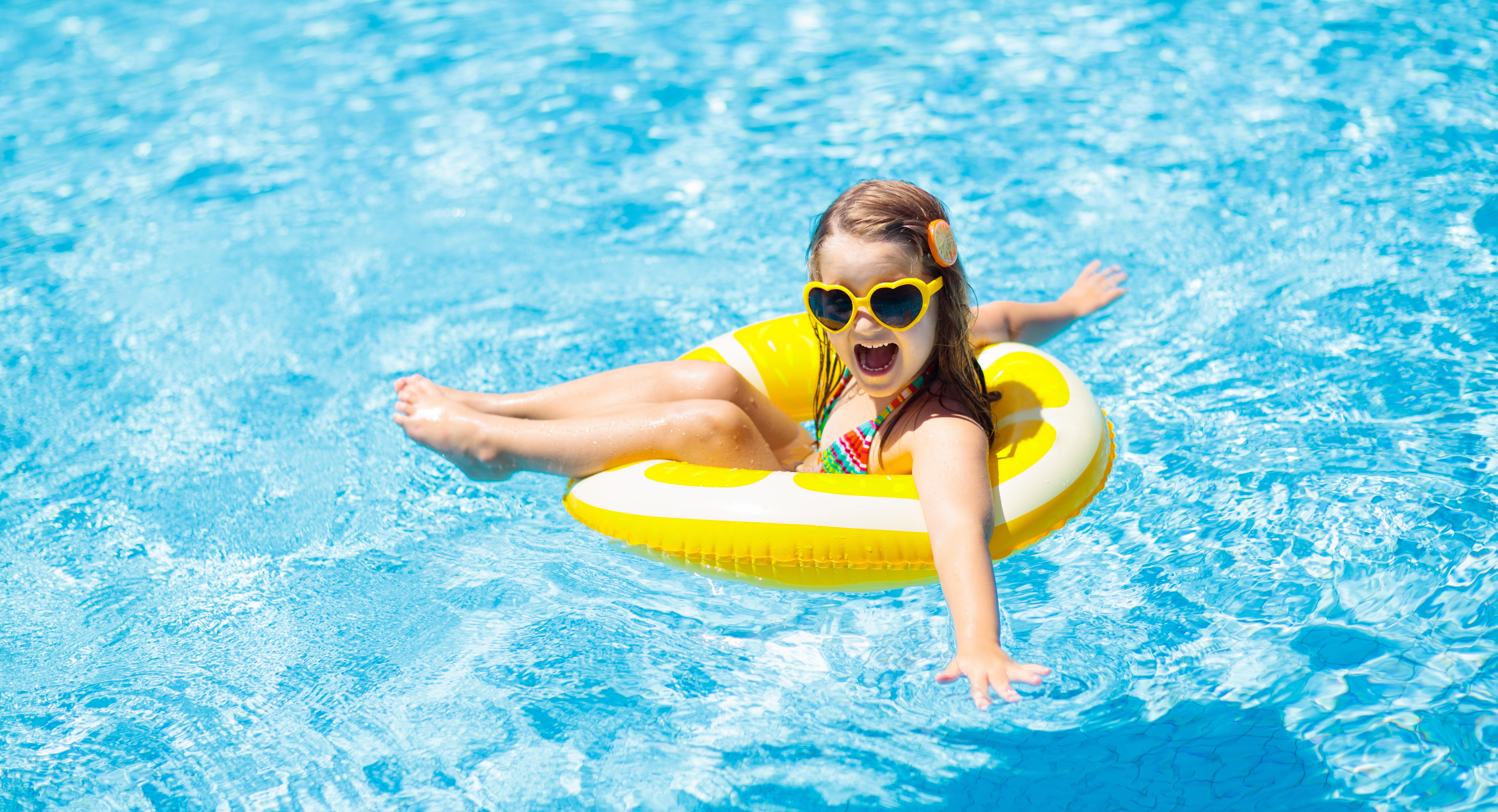 Barn i simbassäng på ringleksak. Barn simmar.